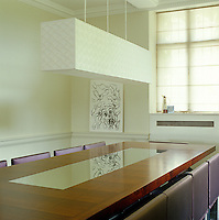 In the dining room the walnut and mirror dining table is designed by Pip Isherwood and the long silk pendant light is by Bruno Triplet