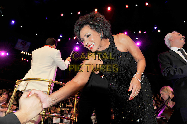 DAME SHIRLEY BASSEY.The Beatles Philharmonic Tribute at the Royal Albert Hall, London, England..October 28th, 2010.stage concert live gig performance music half length black dress paillettes hands shaking .CAP/MAR.© Martin Harris/Capital Pictures.