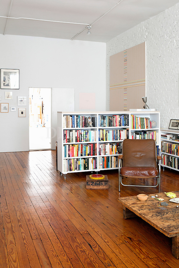 white bookcase<br /> <br /> New York abstract artist, Betsy Kaufman, lives in a 2300 sq. ft loft in the Tribeca area of New York City. Forty percent of the space is used as her studio and sixy percent as her living space.  The loft is decorated with her own artwork as well as artwork from other artists she admires.