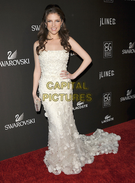 ANNA KENDRICK.The 12th Annual Costume Designers Guild Awards held at The Beverly Hilton Hotel in The Beverly Hills, California, USA. .February 25th, 2010 .full length white lace strapless dress train hand on hip sheer petals applique silver clutch bag.CAP/RKE/DVS.©DVS/RockinExposures/Capital Pictures.
