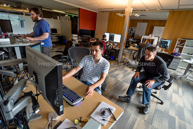 6/18/2012--Bellevue, WA, USA..Valve Software's offices in Bellevue, WASH., just east of Seattle. The office is set up as a 'boss less' office that is fluid and non-hierarchical. Desks come with wheels so that they can be easily moved and reconfigured to create new work spaces for new projects. The desks can also be raised or lowered for comfort or to create a standing work space...Here, Valve employees working, including John Cook (right, wheeling over) and Tony Paloma (left) the 8th floor, on networking systems for the games the company makes...Stuart Isett for The Wall Street Journal