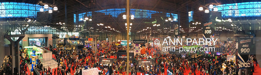 Manhattan, New York City, New York, USA. October 10, 2015. In the vast Block area, crowds of cosplayers and others visit displays, such as a large Batman at left, and vendor booths, such as Truforce, seen in a panoramic overhead view at the 10th Annual New York Comic Con. NYCC 2015 is expected to be the biggest one ever, with over 160,000 attending during the 4 day ReedPOP event, from October 8 through Oct 11, at Javits Center in Manhattan. Captured with iPhone 6S Plus.