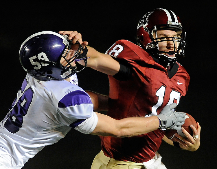Heisman Form -  Harvard Crimson quarterback Andrew Hatch (18), right, stiff arms Holy Cross defender Jimmny Thomas as he carries the ball during the second quarter at Harvard Stadium.
