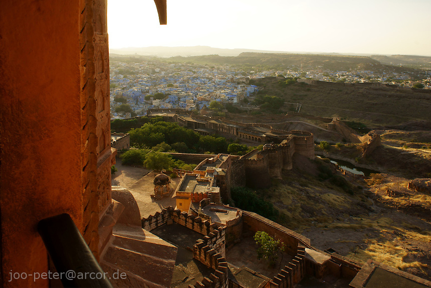 view from a balcony of Fort Mehrangarh, down on blue city Jodhpur, looking North in warm sunset light, Rajastan, India
