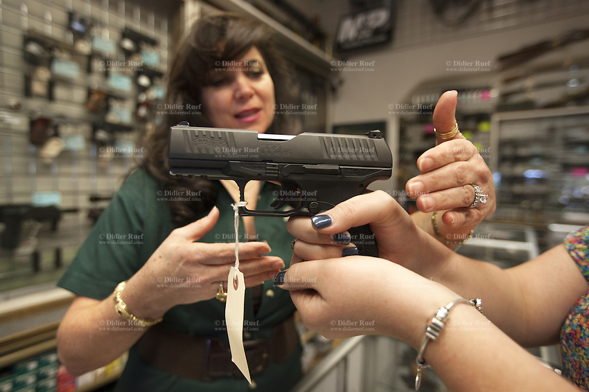 USA. Arizona state. Avondale town. Cheryl Todd is the owner and the manager of the gun shop AZFirearms.com with over 1'000 guns in stock. She stands behind the store's counter and advises a young woman interested in buying a handgun for her personal protection. The woman holds in both her hands a pistol Walther Arms PPQ M2 .45ACP which is one of the finest on a polymer, striker-fired handgun. This gun is a breakthrough in ergonomics for self-defense firearms. The Walther PPQ (PolizeiPistole Quick Defense / Police Pistol Quick Defense) is a semi-automatic pistol developed by the German company Carl Walther GmbH Sportwaffen as a potential replacement for the Walther P99. A firearm is a portable gun, being a barreled weapon that launches one or more projectiles often driven by the action of an explosive force. Most modern firearms have rifled barrels to impart spin to the projectile for improved flight stability. The word firearms usually is used in a sense restricted to small arms (weapons that can be carried by a single person). The right to keep and bear arms is a fundamental right protected in the United States by the Second Amendment of the Bill of Rights in the Constitution of the United States of America and in the state constitutions of Arizona and 43 other states. 25.01.16 © 2016 Didier Ruef