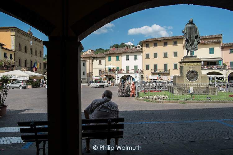 Man sitting in the town square, Greve in Chianti, Tuscany, Italy.