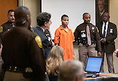 Sniper suspect Lee Boyd Malvo, center, is surrounded by deputies as he is brought into court to be identified by a witness during the trial of sniper suspect John Allen Muhammad in courtroom 10 at the Virginia Beach Circuit Court in Virginia Beach, Virginia, Wednesday October 22, 2003.  Witness Muhammad Rashid, a Maryland Liquor store owner was the witness on the stand when Malvo was brought in. <br /> Credit: Davis Turner - Pool via CNP