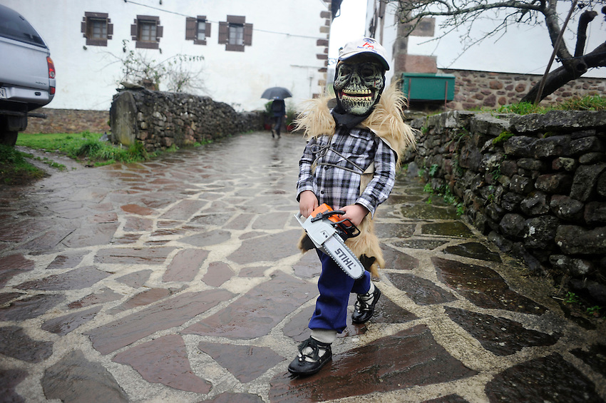 A masked child performs during an ancienta carnival on January 27, 2014 at the village of Ituren, Basque Country. Joaldun groups perform an ancient traditional carnival at the villages of Ituren and Zubieta during two days, carrying sheep furs and big cowbells in their backs and making sound them in order to wake up the earth, to ask for a good new year, a good harvest and also to keep away the bad spirits. (Ander Gillenea / Bostok Photo)