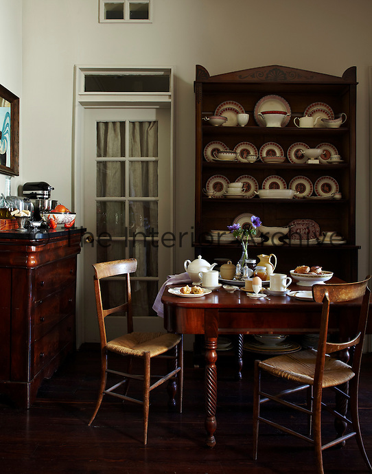 The kitchen is furnished with  a mahogany sideboard and a dresser displaying a collection of creamware