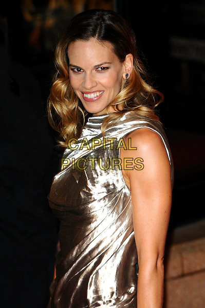 "HILARY SWANK .Attending the 54th BFI London Film Festival screening of ""Conviction"" at Vue cinema, Leicester Square, London, England, UK, October 15th 2010.LFF half length dress  silver gold smiling shiny sleeveless metallic wavy hair .CAP/CJ.©Chris Joseph/Capital Pictures."