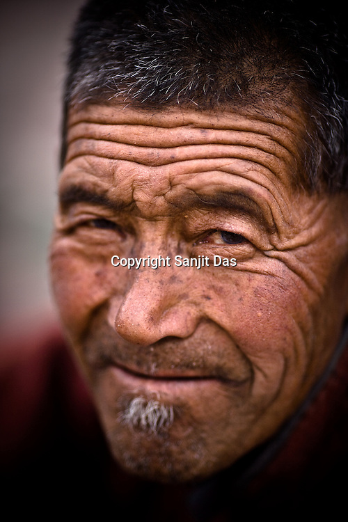 """73 year old, Tashi Wangyal, a local villager waits for His Holiness the Twelfth Gyalwang Drukpa, the head of the Drukpa Lineage to arrive in the outskirts of Hemis in Shwang. """"Walking On The World's Rooftop"""" Pad Yatra from Manali to Ladakh, of 400kms was focused at raising awareness awareness of His Holiness' charitable projects including education , environment and cultural preservation of tribal people from the area. Accompanied on the Yatra by large numbers of Buddhist monks, nuns, foreigners and local villagers. The culmination of the Pad Yatra coincides with the colourful age-old Hemis festival in Leh, Ladakh, India."""