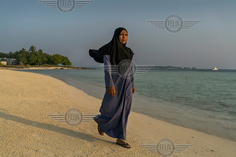 A woman walks along the beach on the inhabited island of Guraidhoo.