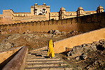 India, Jaipur, Historical City, woman in yellow saree walking up stairs to Jaipur Fort
