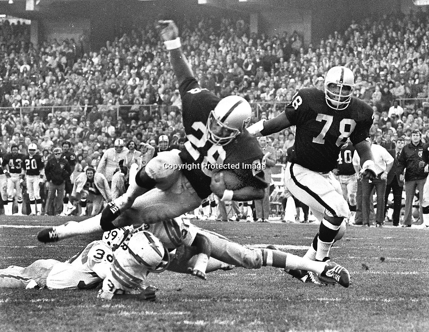 Raiders Clarence Davis scores over couple of fallen San Diego Chargers. #78 Art Shell. (1971 photo ny Ron Riesterer)
