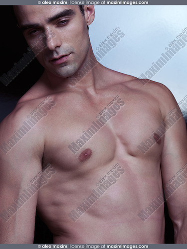 Portrait of a sexy young handsome man with muscular bare torso looking down