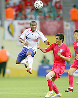 Florent Malouda (7) of France beats Jin Cheul Choi (4) of Korea to a high ball. The Korea Republic and France played to a 1-1 tie in their FIFA World Cup Group G match at the Zentralstadion, Leipzig, Germany, June 18, 2006.