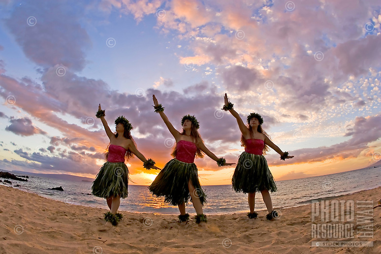 Three hula dancers in ti leaf skirts dance on the beach at sunset at Makena, Maui.