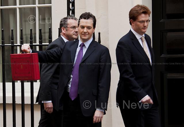 George Osborne (UK Chancellor of the Exchequer) <br /> <br /> London, 23/03/2011. UK Prime Minister David Cameron leaves 10 Downing Street on Budget Day. He is followed by  the Chancellor of the Exchequer, George Osborne, who (followed by his team) shows the &quot;red box&quot; (Budget Box) containing the Budget for the fiscal year. In the meanwhile, outside the gates of Downing Street, protesters gather for a variety of demonstrations. The demands of protesters included an end to the Government budget cuts and austerity measures and a stop to cuts in the NHS.