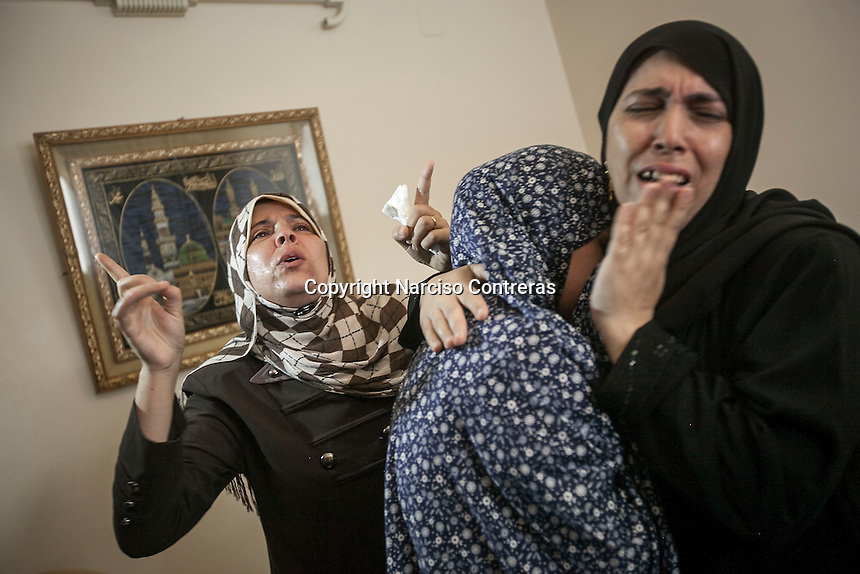 """August 24, 2014 - Gaza City, Gaza strip, Palestinian Territory: Relatives mourn the dead of Palestinian boy Mohammed Al Khodary, 17 years-old (not pictured) during his funeral after an aistrike targeted the Al -Nafak area in Gaza City as """"Protective Edge"""" Israeli military operation continues in the Gaza strip. (Narciso Contreras/Polaris)"""