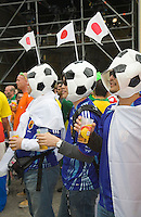 Germany, DEU, Dortmund, 2006-Jun-22: FIFA football world cup (USA: soccer world cup) 2006 in Germany; three Japanese football fans wearing hats looking like balls at a public viewing zone.