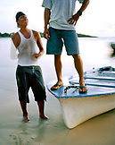 HONDURAS, Roatan, young boat drivers standing by waters edge