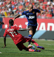 Chicago Fire midfielder Patrick Nyarko (14) slide tackles the ball away from Manchester United midfielder Gabriel Obertan (26).  Manchester United defeated the Chicago Fire 3-1 at Soldier Field in Chicago, IL on July 23, 2011.