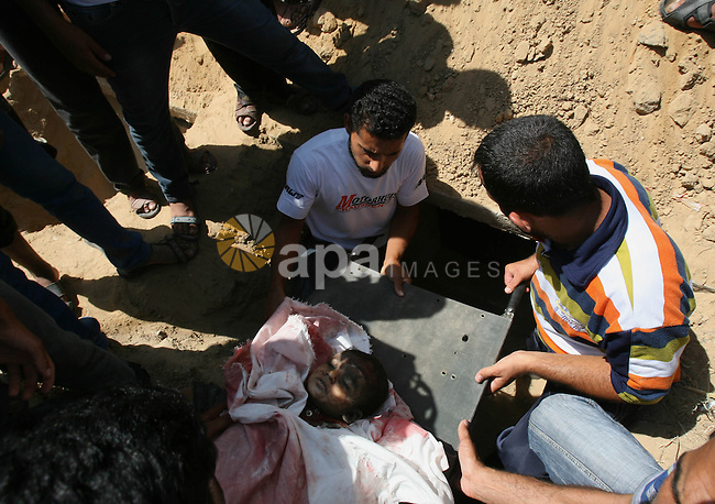 Palestinians bury the body of a boy from the al-Najar family, who medics said was killed with other family members by an Israeli air strike on their house, at a cemetery in Khan Younis in the southern Gaza Strip July 26, 2014. The Gaza Health Ministry said 18 members of a single family were killed by Israeli tank shelling in the southern Gaza Strip shortly before the truce took effect at 8 a.m. (6 a.m. British Time). An Israeli military spokeswoman said she was checking the report. A 12-hour humanitarian truce went into effect on Saturday after Israel and Palestinian militant groups in the Gaza Strip agreed to a U.N. request for a pause in fighting and efforts proceeded to secure a long-term ceasefire moved ahead. Photo by Eyad Al Baba