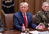 United States President Donald J. Trump answers a reporter's question as he participates in a briefing with senior military leaders in the Cabinet Room of the White House in Washington, DC on Monday, October 7, 2019.  At right is United States Army General Mark A. Milley, Chairman of the Joint Chiefs of Staff.<br /> Credit: Ron Sachs / Pool via CNP