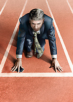 Businessman with money tie on starting line of athletics track