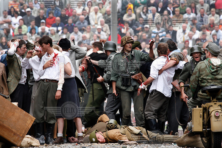 Actors take part in a battle re-enactment to commemorate the 63rd anniversary of the Warsaw Uprising during World War II (WW2).