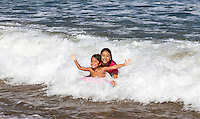 A local brother and sister ride a wave on a boogie board at Hanalei Bay off of Hanalei Beach, Kaua'i.