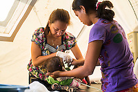 Nurse Sharon Pacaldo (left), of the Philippine Red Cross, treats at a severely dehydrated child as the mother assists in the emergency medical tent for evacuees in the city's largest stadium in Zamboanga, Mindanao, The Philippines on November 5, 2013. These Internally Displaced People (IDP) had taken refuge in this stadium after surviving the 3 week long attack by MNLF rebels. Photo by Suzanne Lee for SPRINT-IPPF