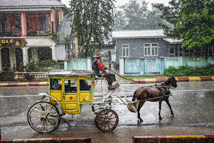 Man driving an unique horse carriage under the rain in Pyin Oo Lwin; formerly known as May Myo during British colonial  occupation is a scenic hill town in Mandalay Division, Myanmar.