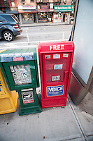A Village Voice distribution box is seen with other newspaper boxes in New York on Monday, October 12, 2015. Voice Media Group has sold their eponymous weekly to to a company controlled by Peter Barbey of the Reading Eagle Company for an undisclosed sum. The VV has was founded in 1955 and VMG acquired it in 2005. (© Richard B. Levine)