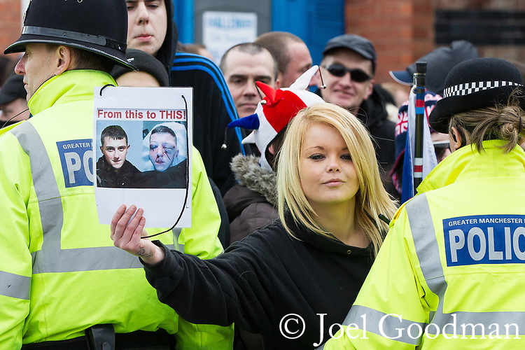 © Joel Goodman - 07973 332324 . 25/02/2012 . Hyde , UK . A woman holds up before and after photos of Daniel Stringer-Price . The EDL demonstrate following an assault on Daniel Stringer-Prince, whose family say they do not want the demonstration to take place in the town in their son's name. The EDL say Daniel was assaulted by a gang of Asian men . At the same time , the BNP hold a rally in the town . Photo credit : Joel Goodman