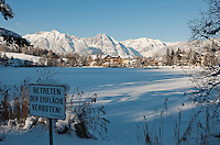 Austria, Tyrol, international Wintersport Resort Seefeld: frozen Wild Lake and Wetterstein mountains, Hotel Seespitz at background