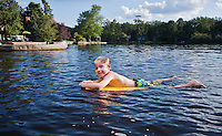 Little boy floating on a body board in a public lake