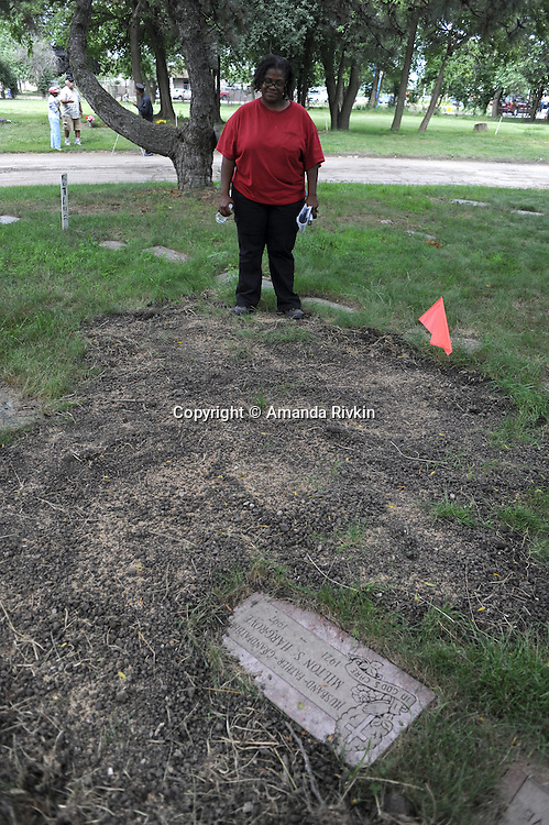 Michelle Hargrove, 40, beside what appeared to be fresh earth where Hargrove said her mother had previously been buried at the Burr Oak Cemetery, one of the oldest and most historic black American cemeteries on the outskirts of Cook County, the same day four cemetery managers and caretakers were arrested on felony charges of disinterring and dismembering bodies at the cemetery in order to resell the plots to unsuspecting members of the public in Alsip, Illinois on July 9, 2009. In recent months, many older graves had reportedly been moved and relocated within the cemetery grounds adding to the forensics confusion.