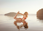 Young woman practicing yoga on a floating platform in water on the lake during misty sunrise in the morning. Yoga Bow posture, Dhanurasana. Muskoka, Ontario, Canada.