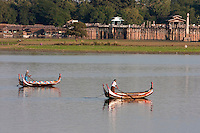 Myanmar, Burma, Mandalay.  Taungthaman Lake.  Two Boats in Afternoon Sun, U Bein Bridge in Background.