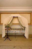 A small metal-framed daybed with a muslin canopy