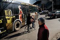 An advertisement for Monarch brand toilets depicting a urinating boy covers the side of a bus in Nanjing, Jiangsu, China.