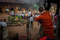 December 04, 2013 - Kampong Thom, Cambodia. A monk photographs children lining up for school on the third day of a 10-day Human Rights march. © Luc Forsyth / Ruom