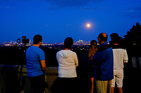 EAGLE ROCK, NJ - JUNE 09: People take a look of the Strawberry Moon as it rises over lower Manhattan next to One World Trade Center on June 06, 2017 in Montclair, New Jersey. Photo by VIEWpress/Eduardo MunozAlvarez