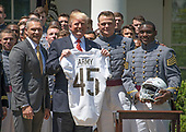 United States President Donald J. Trump presents the Commander-in-Chief's Trophy to the U.S. Military Academy football team in the Rose Garden of the White House in Washington, DC on Tuesday, May 1, 2018.  The Commander-in-Chief's trophy is presented to the winner of the annual Army-Navy football game which was played at Lincoln Financial Field in Philadelphia, Pennsylvania on December 9, 2017. Pictured from left to right: Head coach Jeff Monken, President Trump, defensive lineman and co-Captain John Voit (59), and quarterback and co-Captain Ahmad Bradshaw (17). The Army Black Knights beat the Navy Midshipmen 14 - 13.  <br /> Credit: Ron Sachs / CNP