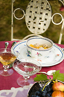 Pretty crockery and delicate glassware make a beautiful still-life on the table of this al fresco lunch