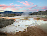 Yellowstone National Park, Wyoming:<br /> Mammoth Hot Springs upper terrace. Travertine patterns and thermal steam under sunset colored sky