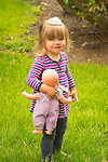 Toddler with doll baby and hat.