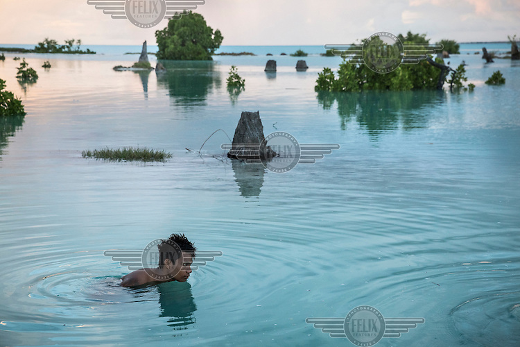 Peia Kararaua, 16, swims in the flooded area of Aberao village. Kiribati is one of the countries most affected by sea level rise. During high tides many villages become inundated making large parts of them uninhabitable.