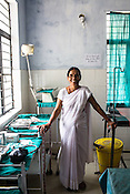 57 year old Usha Srivastava poses for a photo at the delivery room of the Public Health Centre in Adapur village of Raxaul district of Bihar.